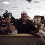 A man, who is hoping to cross into Egypt, shouts as he holds his passport and other family members' passports while he waits at the Rafah crossing between Egypt and the southern Gaza Strip
